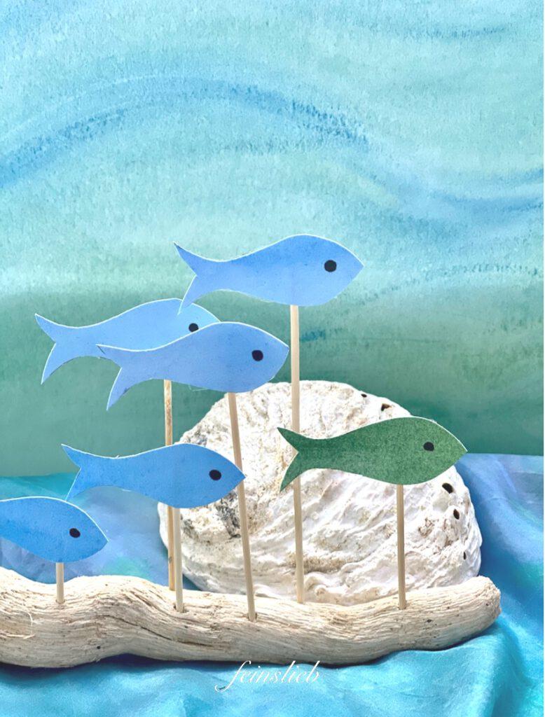 hellblaue und grüne Fische, vor hellgrün-hellblauem, sanften Wassermotiv, nah