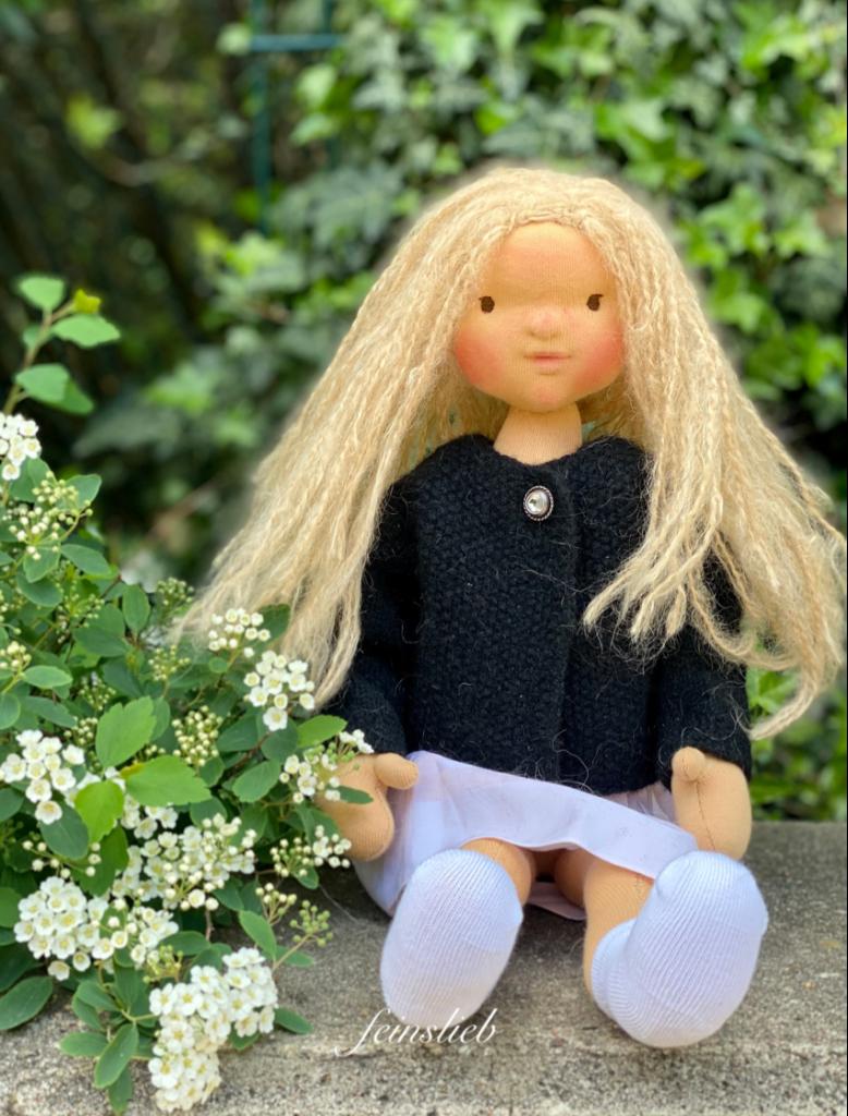 Puppe sitzt neben Prachtspeere-Blüten