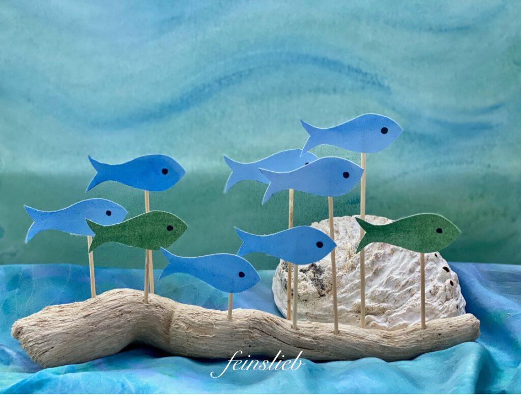 Jahreszeitentisch Sommer: Schwemmholz-Ast mit hellblauen und grünen Fischen, vor hellgrün-hellblauem, sanften Wassermotiv