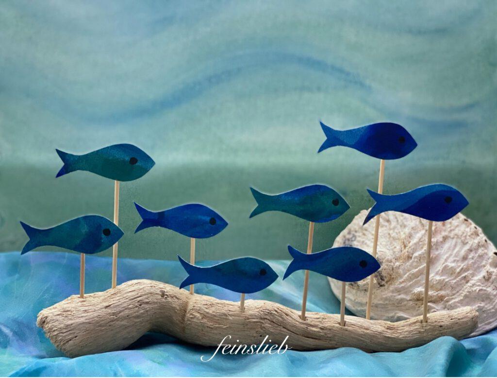 Eine schöne Idee für den Jahreszeitentisch Sommer: heller Schwemmholz-Ast mit dunkelblauen Papierfischen eingesteckt, vor Wassermotiv auf Aquarellpapier