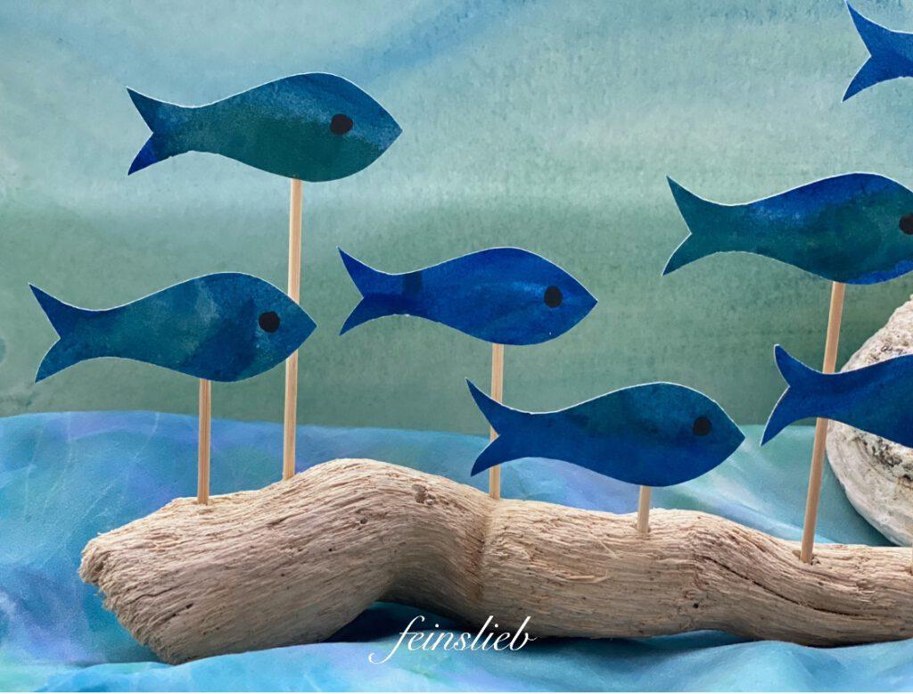 dunkelblaue Fische, vor hellgrün-hellblauem, sanften Wassermotiv