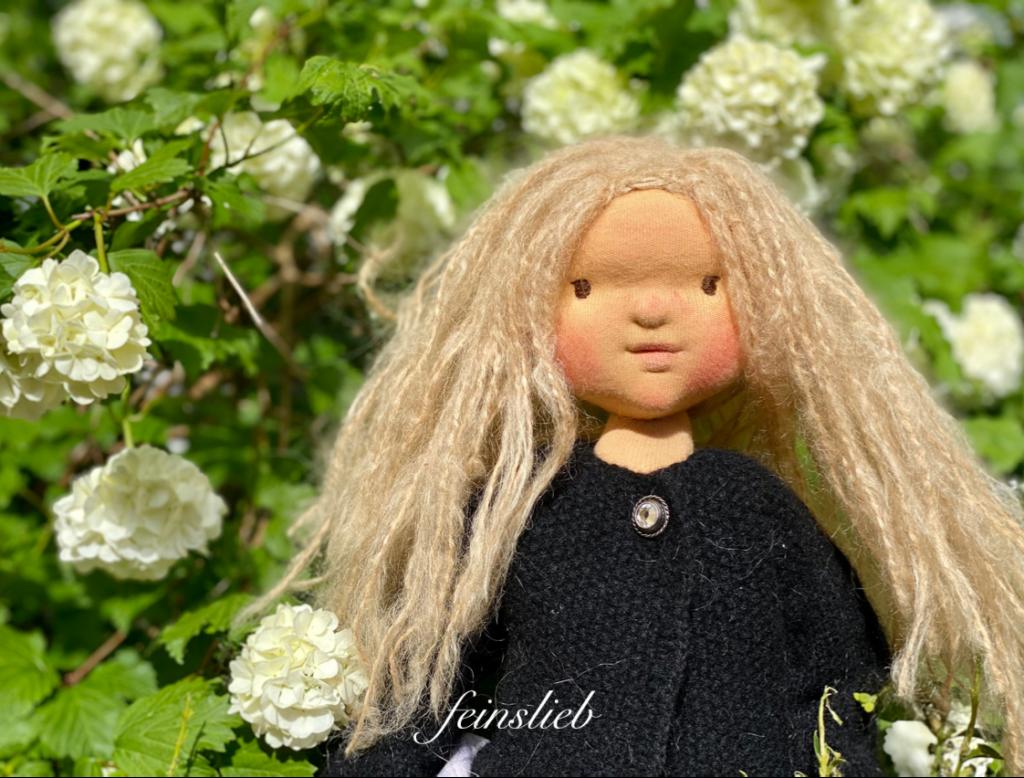 Puppe entwerfen: Puppenkopf mit langen blonden Haaren und braunen gestickten Augen vor blühenden Schneeball-Hortensien