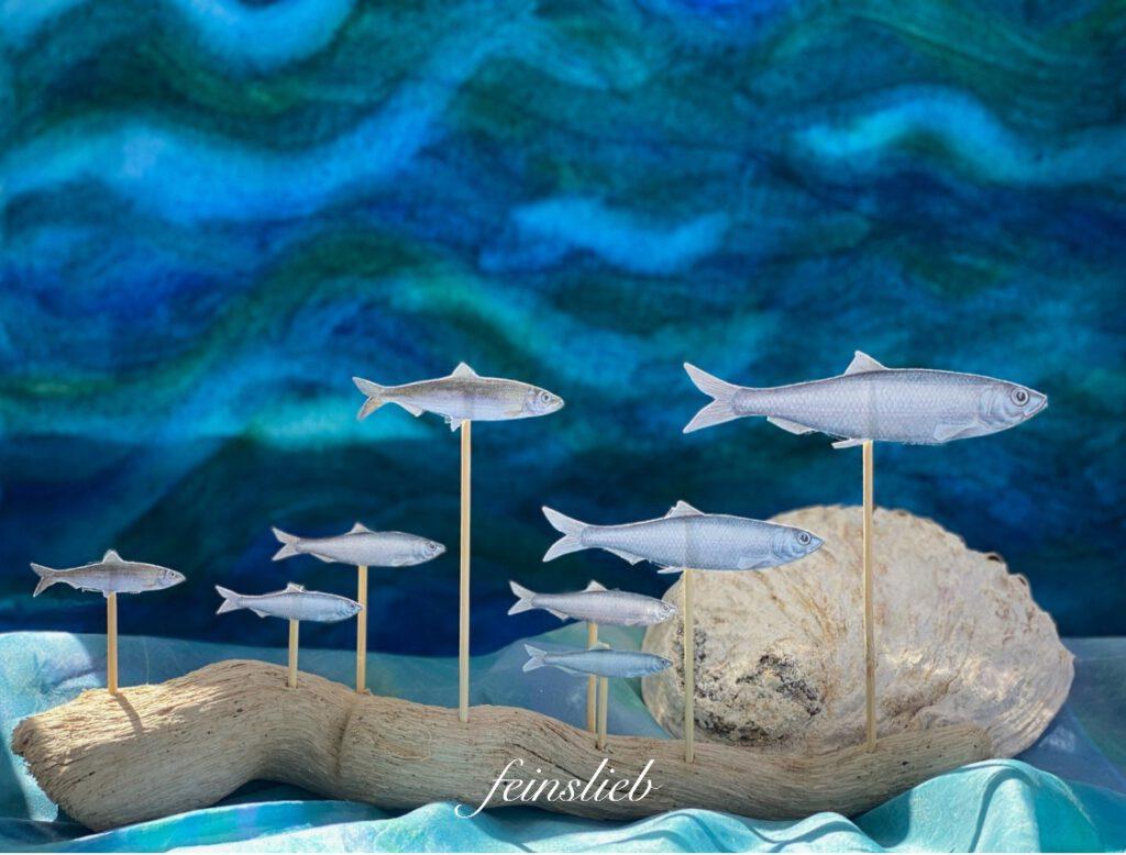 Jahreszeitentisch Sommer: heller Schwemmholz-Ast mit silbernen Heringen, vor dunklem, bewegtem Wassermotiv