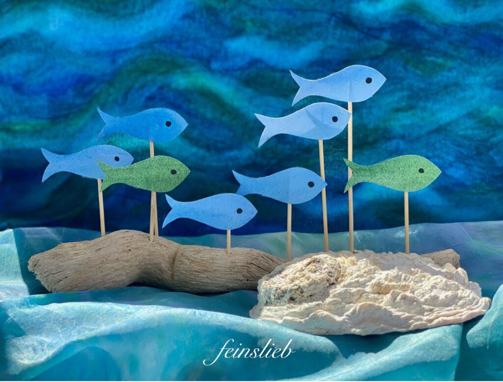Jahreszeitentisch Sommer: heller Schwemmholz-Ast mit hellblauen und hellgrünen Fischen, vor dunklem, bewegtem Wassermotiv