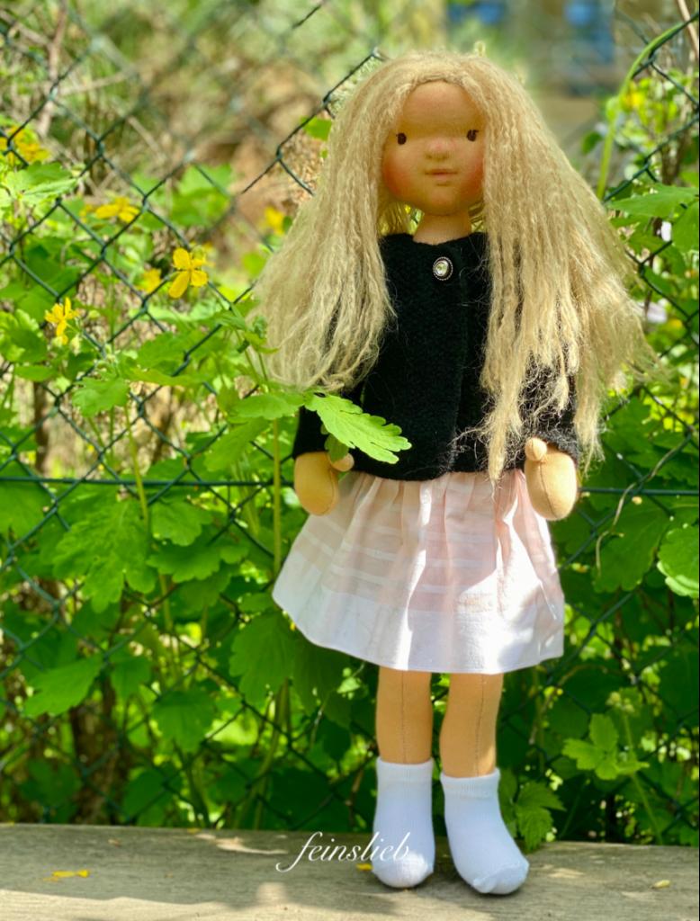 Stehende Puppe vor Grün und Blumen
