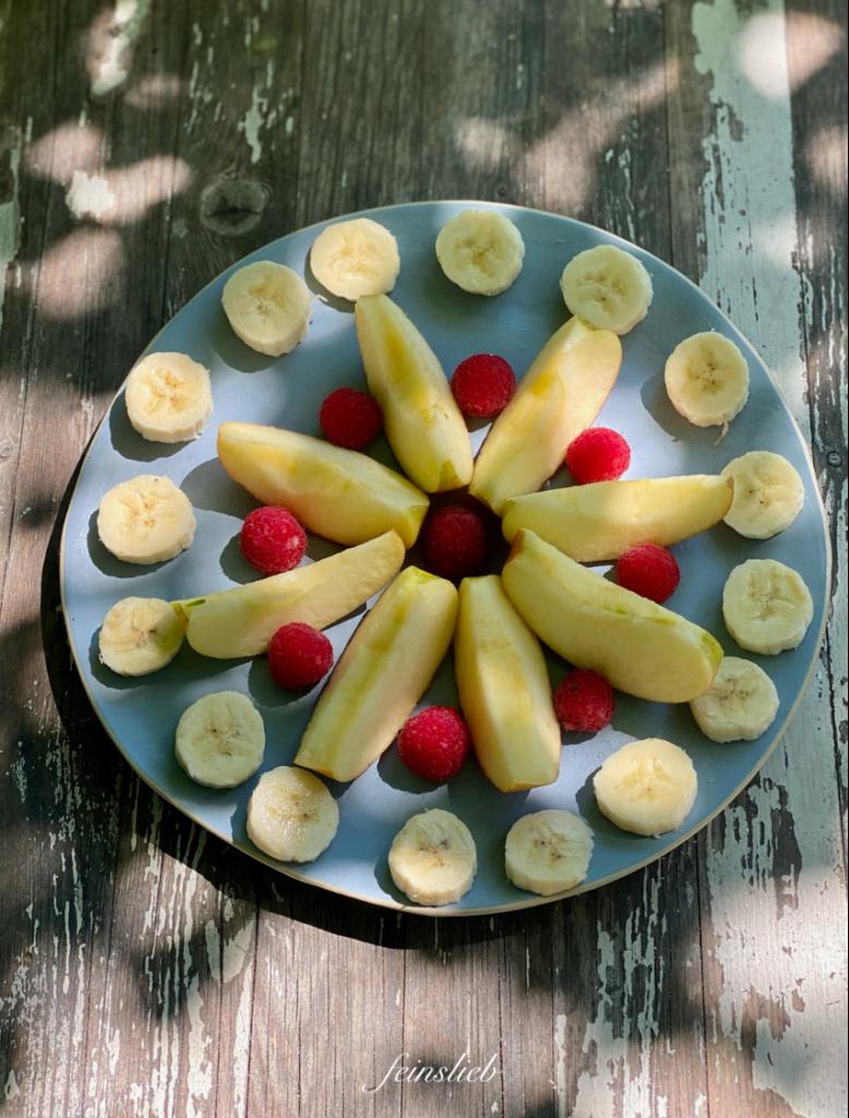 """Obstteller von oben, auf dem Apfelschnitze sonnenstrahlartig angeordnet sind. Zwischen den Äpfeln Himbeeren, an den """"Spitzen"""" der Äpfel Bananenscheiben."""