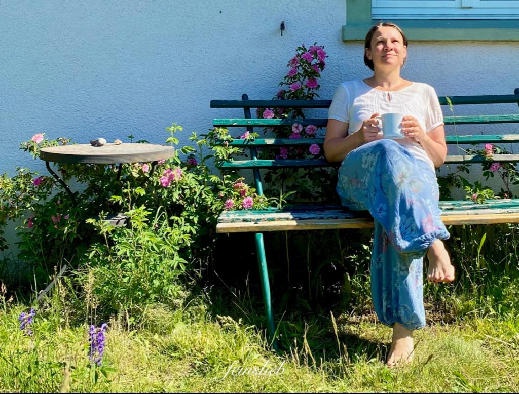 Ich sitze auf einer Gartenbank, neben mir blühen Wildrosen, ich halte eine Tasse Tee und schaue in den Himmel.