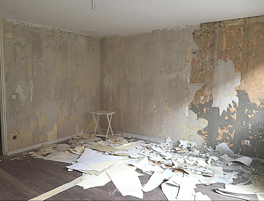 Tapeten abziehen in Wohnung in Berlin: Zimmer mit Blick auf die Ecke, an der Wand wurden Tapeten abgezogen. Auf dem Boden liegen Tapetenreste.