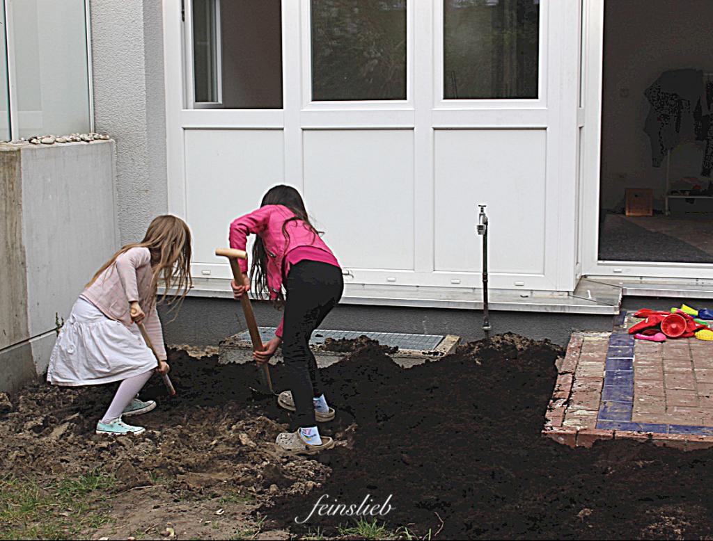 Umgestaltung des Gartens der Wohnung in Berlin: 2 Kinder vermischen mit Spaten dunkelbraune Erde mit hellerer Erde