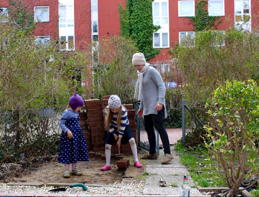 Umgestaltung des Gartens der Wohnung in Berlin: 2 Kinder hebeln Steinplatten aus dem Sandboden.