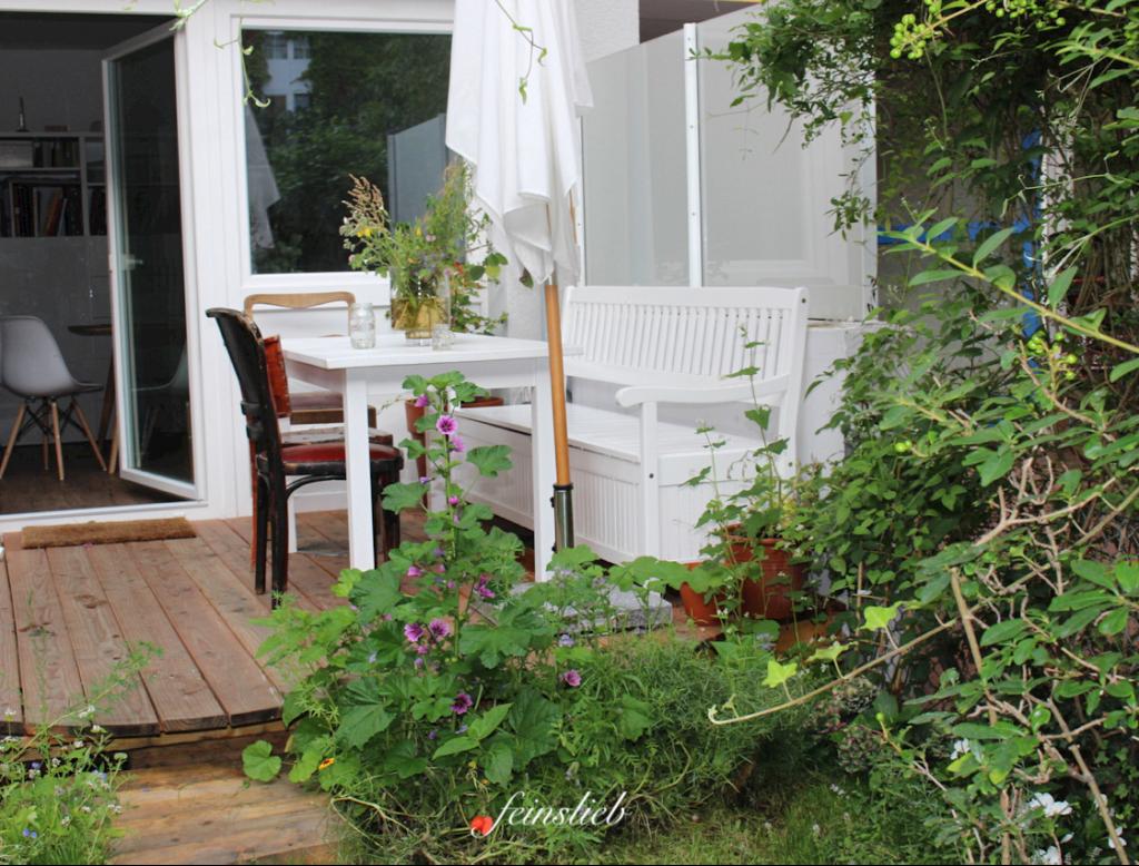 Terrasse aus Holzdielen mit Gartenmöbeln drauf, davor blühen und ranken Blumen