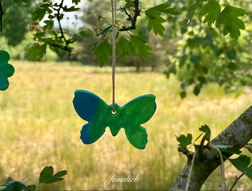 Basteln im Sommer: Ausgestochener Schmetterling, blaugrün bemalt, an Schnur vor Naturlandschaft.