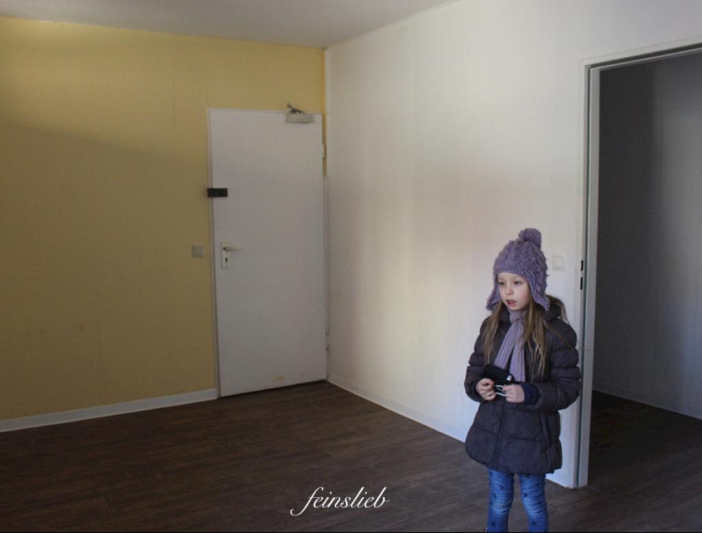 Kind mit lila Mütze und braunem Mantel steht in Zimmer mit gelber Wand in Neubau- Wohnung in Berlin.
