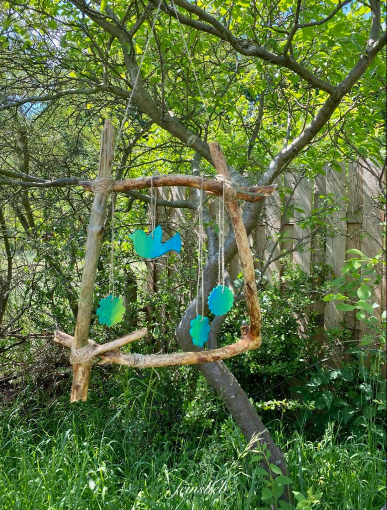 Sommerbastelei an meinem perfekten Tag im Juni 2021: Bilderrahmen aus Ästen mit Schnur an Busch gehängt, vom Bilderrahmen hängen blaugrüne Ausstechformen herunter (Vogel und Blumen)