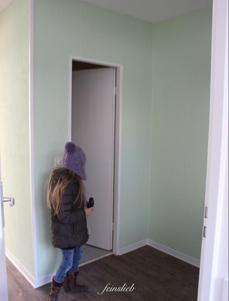Unsere neue Wohnung in Berlin vor der Renovierung: Mintgrüne Wände und brauner Boden... Kind mit lila Mütze von hinten schaut in einen Raum.