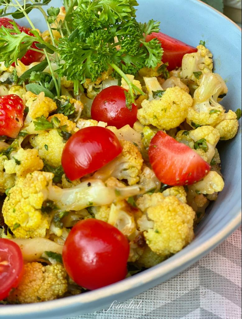 Gemüse-Grill-Rezept: Nahaufnahme orientalischer gegrillter Blumenkohl als Salat mit Cherry-Tomaten und geviertelten Erdbeeren