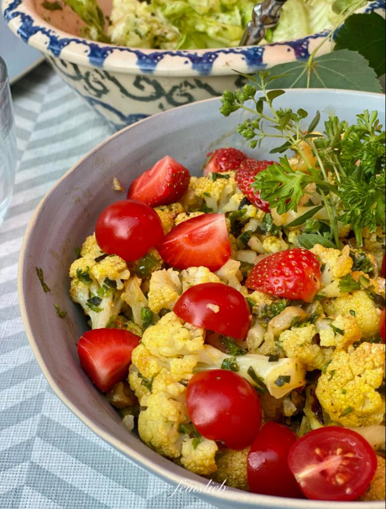 Gemüse Grill Rezept: Salatschüssel mit Blumenkohl-Salat vom Grill auf Tisch, im Hintergrund eine Salatschüssel mit grünem Salat