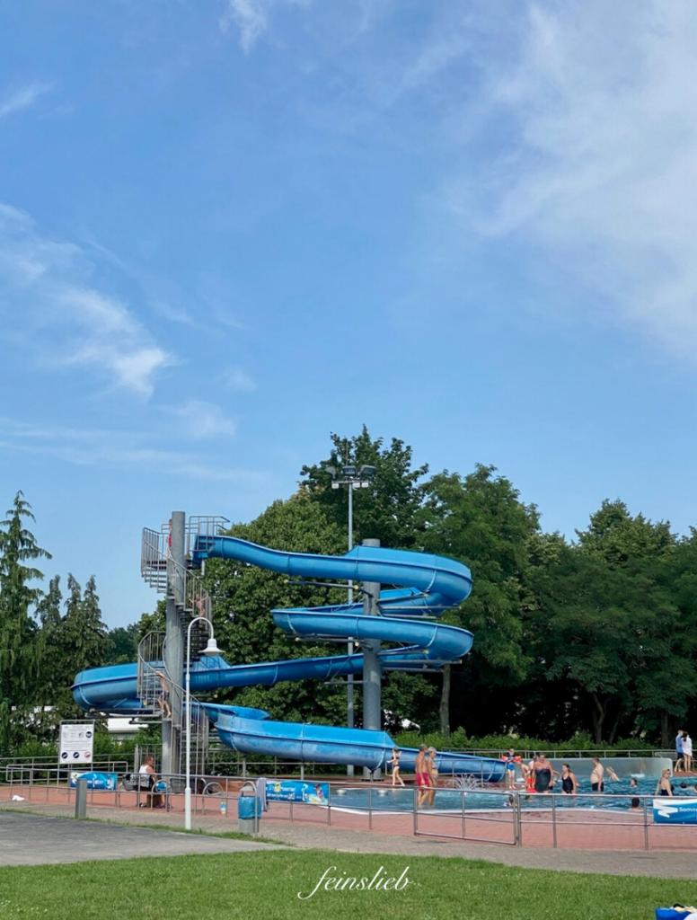 Wasser-Rutsche im Schwimmbad mit blauem Himmel dahinter
