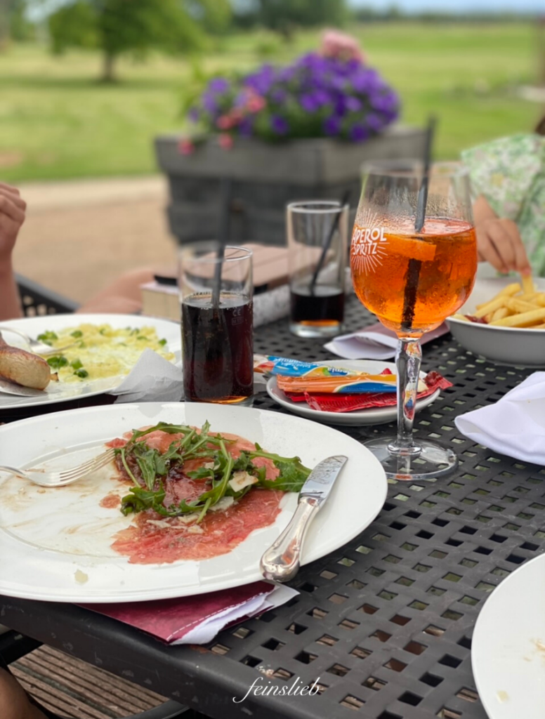 Tisch mit Park im Hintergrund. Auf dem Tisch ein Glas mit Aperol Spritz, ein halb aufgegessener Teller mit Rinder-Carpaccio und im Hintergrund ein Teller Pommes und 2 Cola-Gläser