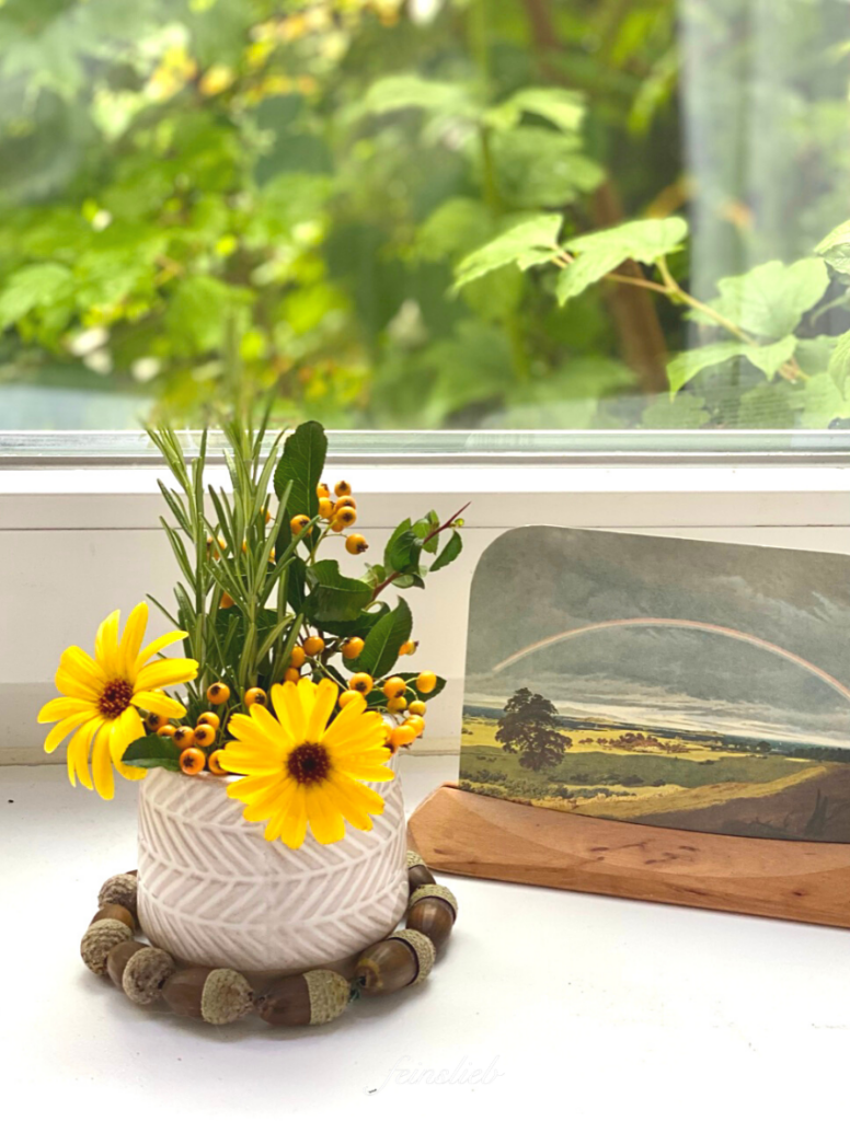 Postkarte mit Regenbogen über September-Landschaft und Blumenvase mit Ringelblumen, hellorangenen Beeren und Rosmarin-Zweigen (Jahreszeitentisch September)