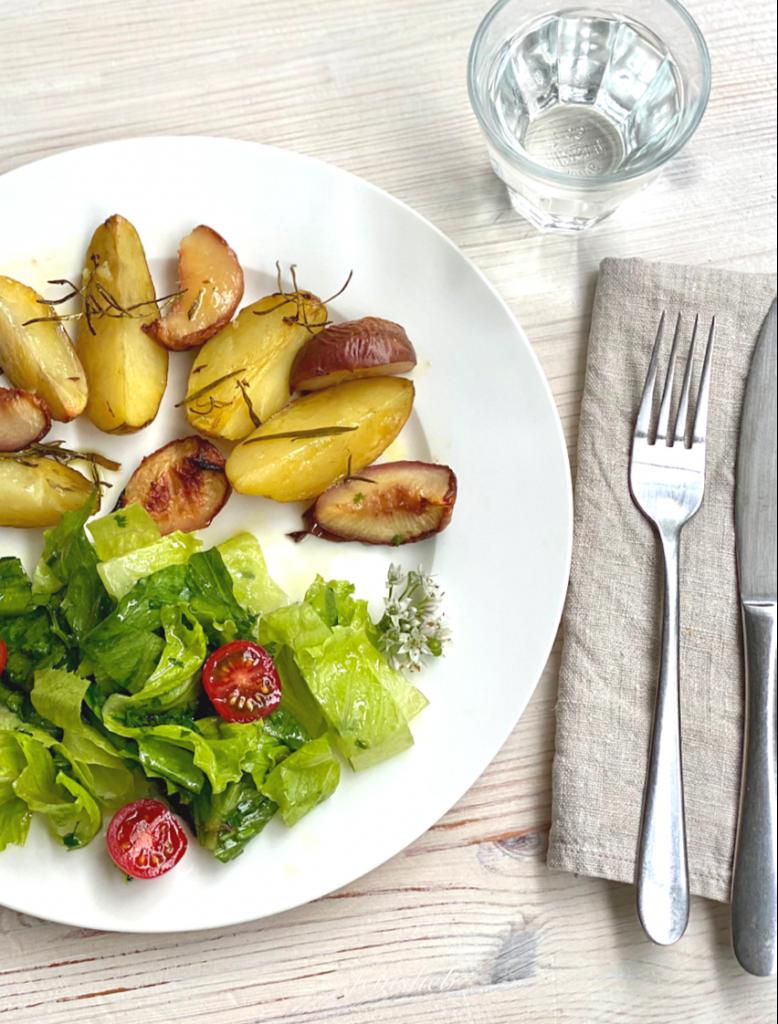 Gebackene Rosmarinkartoffeln mit Pfirsich auf Teller, daneben Besteck, Leinenserviette und Wasserglas