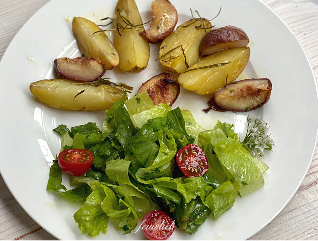 Gebackene Rosmarinkartoffeln mit Pfirsich auf Teller, mit grünem Salat