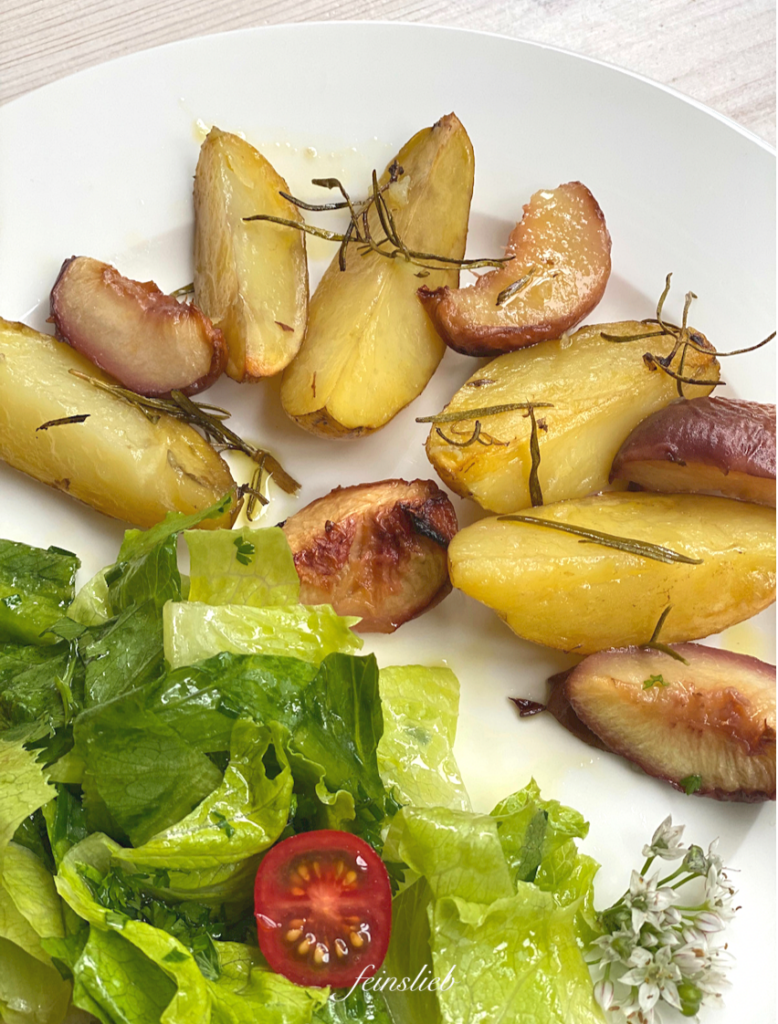 Gebackene Rosmarinkartoffeln mit Pfirsich auf Teller, mit grünem Salat.