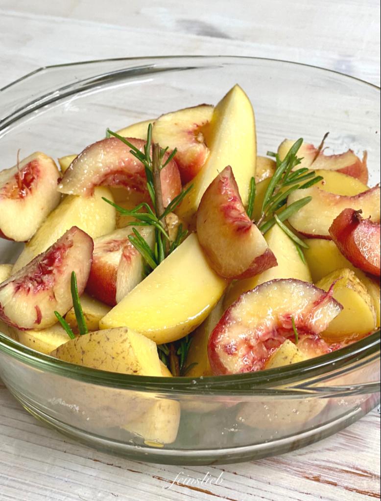 Rosmarinkartoffeln mit Pfirsich -Scheiben in Ofenform aus Glas nah.