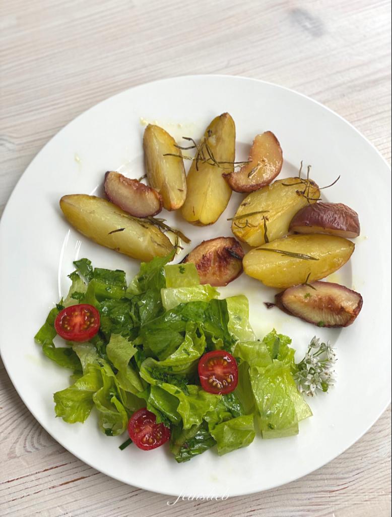 Gebackene Rosmarinkartoffeln mit Pfirsich auf Teller, mit grünem Salat daneben