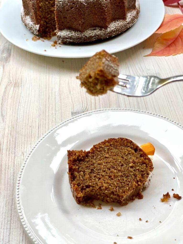 Ein Stück des Kuchens auf weißem Teller, Gabel mit Kuchenstückchen
