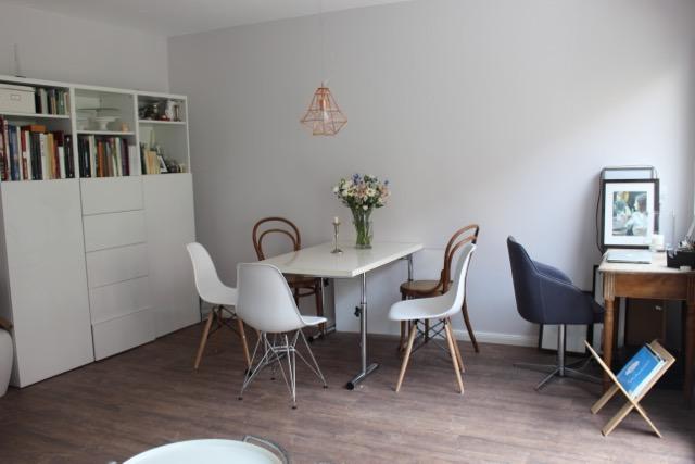 Nach der Renovierung der Wohnung in Berlin: Helle Wände (hellgrau und wei0, weiße Möbel (Regal, Tisch, moderne Stühle