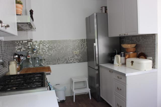hellgrau-weiß gestaltete Küche mit Mosaikfliesen aus silbergrauem Metall und silbernem Kühlschrank