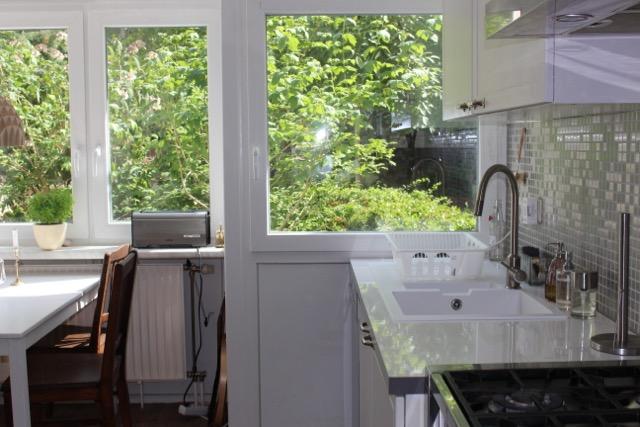 Blick auf Küchenspüle und üppiges Grün vor dem Fenster der Wohnung in Berlin-Wedding
